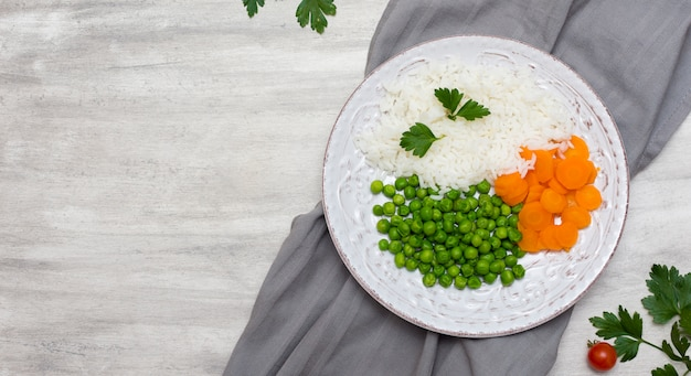 Riz cuit avec des légumes et du persil sur plaque sur un drap gris