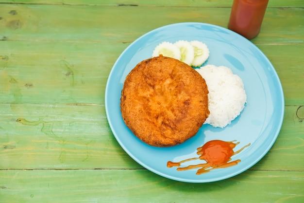 Riz cuit à la vapeur avec du porc haché et une omelette moelleuse dans un plat posé sur la table verte.