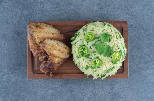 Riz cuit à la vapeur avec des morceaux de poulet sur planche de bois.