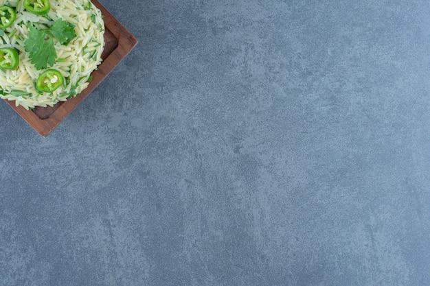Riz cuit à la vapeur savoureux sur planche de bois.