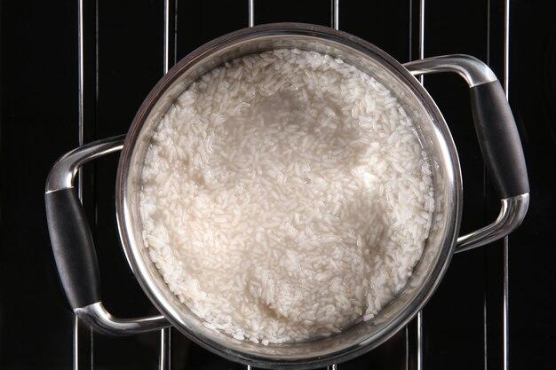 Riz dans la casserole en métal sur la plaque chauffante