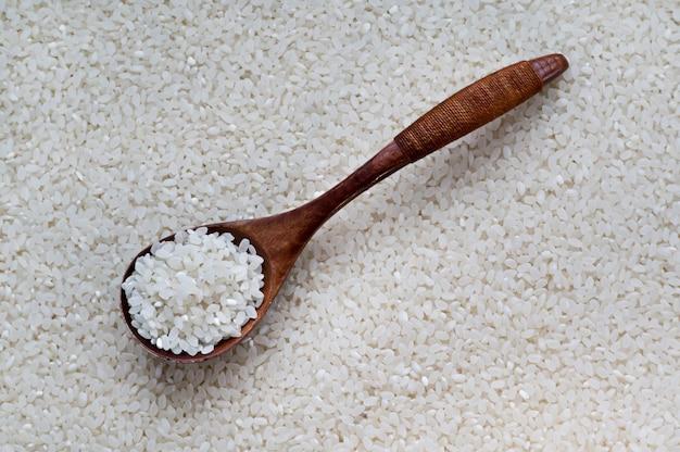 Riz dans une cuillère en bois sur fond blanc, vue de dessus. texture de riz cru non cuit à grains longs blanc