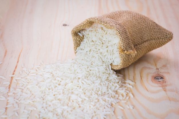 Riz dans un sac de jute verser sur une surface en bois