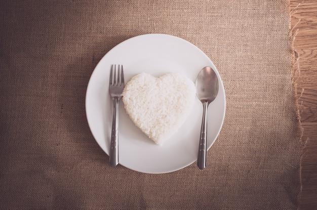 Riz en forme de coeur sur plaque blanche