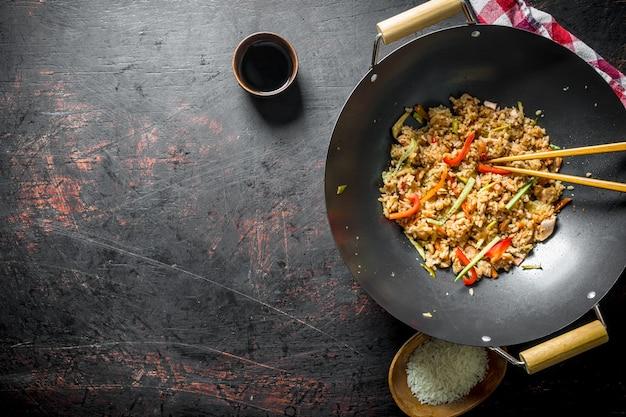 Riz fraîchement cuit avec des légumes dans un wok avec du riz cru sur une assiette et de la sauce soja. sur rustique foncé