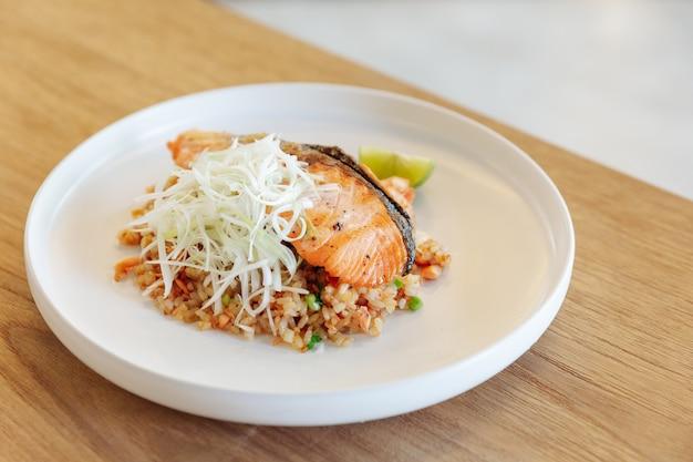 Riz frit à l'ail avec du saumon grillé sur fond de table en bois.