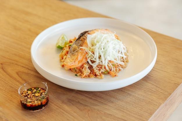 Riz frit à l'ail avec du saumon grillé servi avec une sauce aux haricots pimentés sur une table en bois.