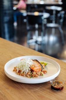 Riz frit à l'ail avec du saumon grillé sur une table en bois avec arrière-plan flou.