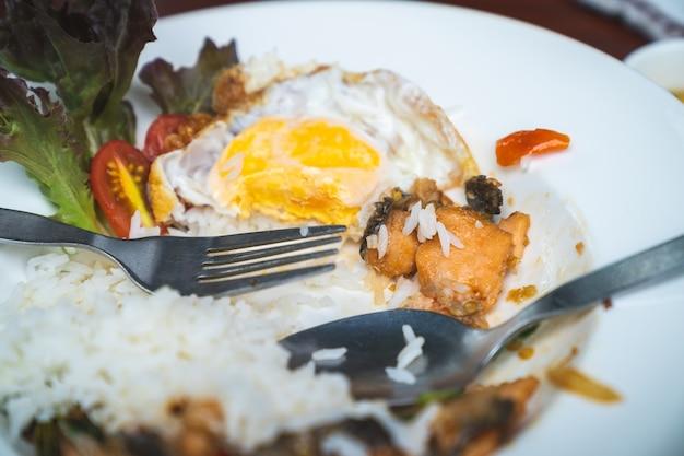 Riz frit au basilic avec œuf sur le plat sur une plaque blanche qui est consommée