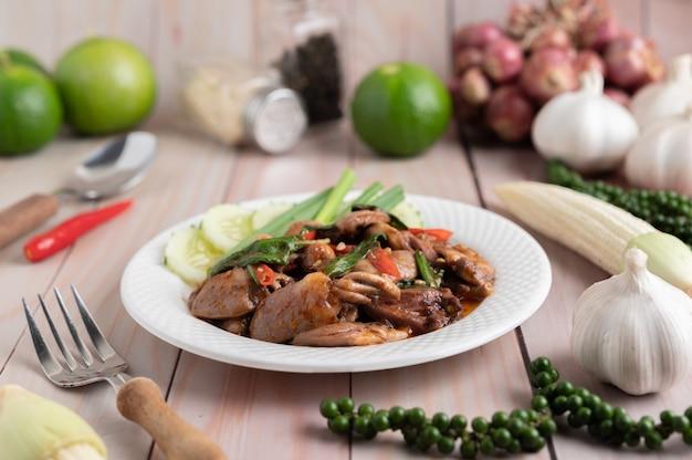 Riz frit au basilic sacré avec coeur de poulet sur un plancher en bois blanc.