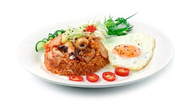 Riz frit au kimchi avec calamars (ojing o bogeum) œufs frits servis de style coréen garni de poireaux