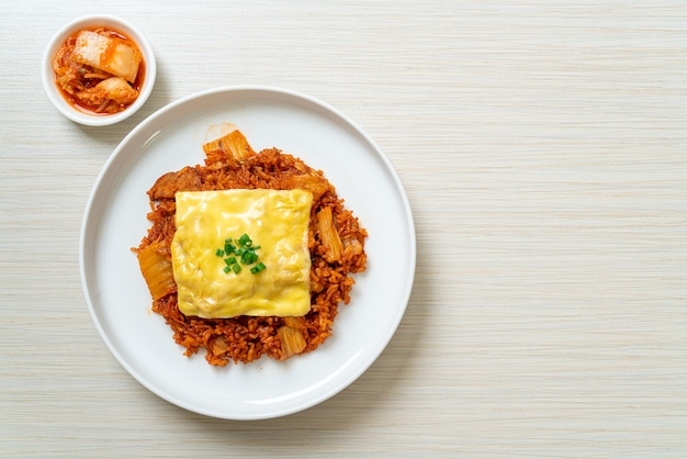 Riz frit au kimchi avec du porc et du fromage garni. style de cuisine asiatique et fusion