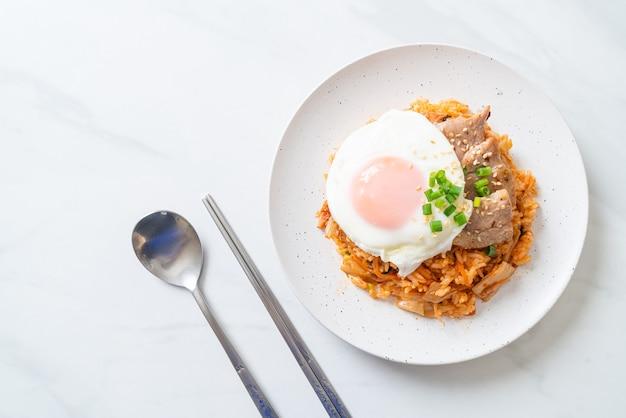 Riz frit au kimchi avec oeuf au plat et porc - style de cuisine coréenne