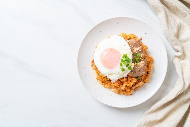 Riz frit au kimchi avec œuf frit et porc - style de cuisine coréenne