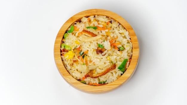 Riz frit au poulet sur un bol en bois