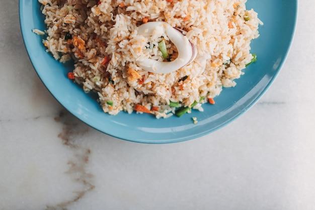 Riz frit aux calmars de style thaï servi dans un plat en céramique bleu