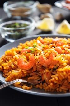 Riz frit aux crevettes, citron et légumes sur une plaque grise