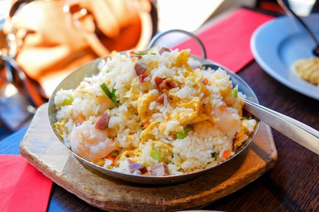 Riz frit aux crevettes dans une poêle chaude utilisée comme assiette avec une table en bois à l'arrière-plan.