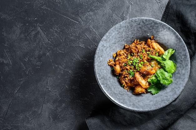 Riz frit aux crevettes préparé au wok. fond noir. vue de dessus. espace copie