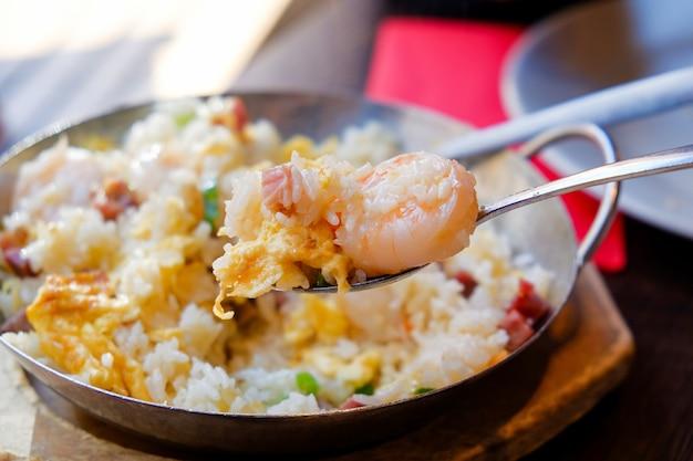 Le riz frit aux crevettes se mange dans une poêle chaude utilisée comme assiette avec une table en bois.