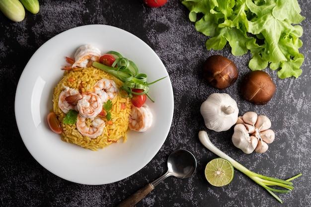 Riz frit aux crevettes avec tomates, carottes et oignons verts dans l'assiette