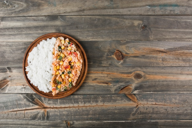 Riz frit blanc et chinois sur une assiette en bois au-dessus de la table