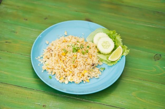 Riz frit avec de la chair de crabe dans les plats mis sur la table verte.