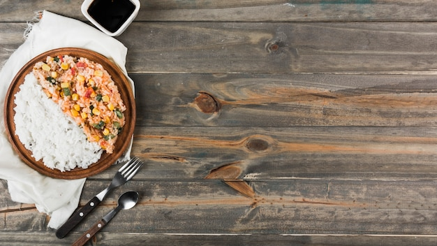 Riz frit et cuit à la vapeur sur une plaque en bois avec une fourchette et une cuillère sur la table