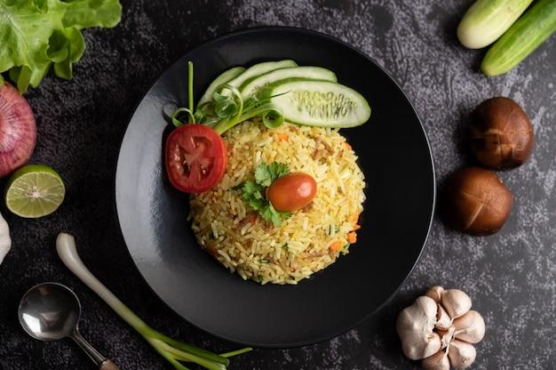Riz frit avec du porc haché, tomate, carotte et concombre dans l'assiette