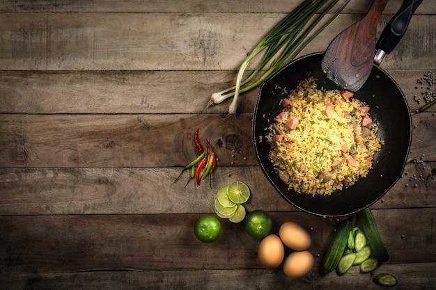Riz frit avec des légumes, de la viande et des œufs au plat servis dans une assiette avec des baguettes