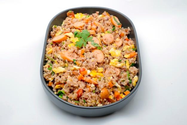 Riz frit avec des saucisses et des légumes sur fond blanc