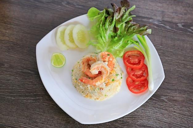 Riz frit à la thaïlandaise avec crevettes sur une assiette blanche contre une table en bois