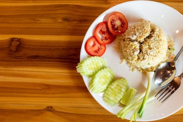 Riz frit à la viande de crabe et légumes sur une table en bois.