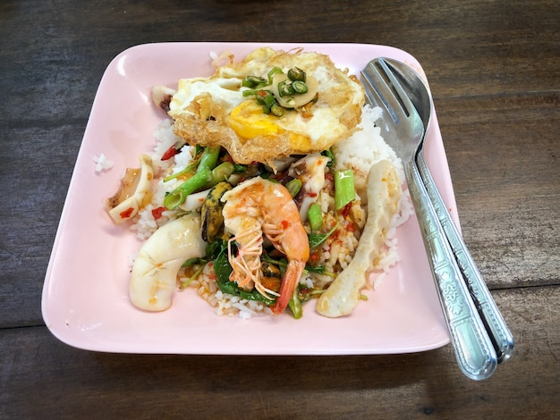 Riz garni de fruits de mer et de basilic avec œuf au plat
