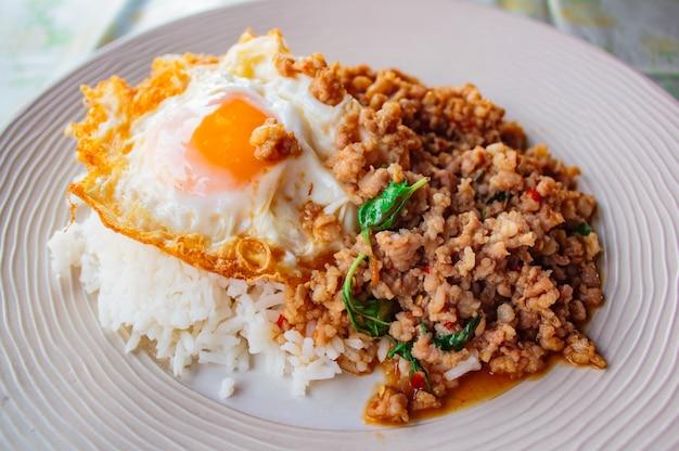Riz garni de porc sauté et de basilic servi avec un œuf au plat.
