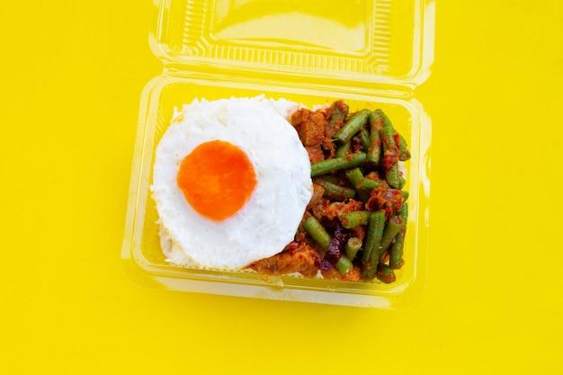 Riz garni de porc sauté épicé et de haricots longs avec pâte de curry rouge, œuf au plat dans un récipient en plastique sur fond jaune.
