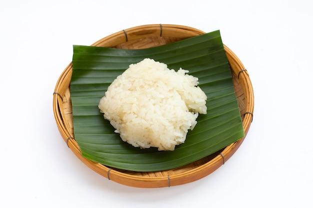 Riz gluant dans un panier en bambou sur fond blanc.