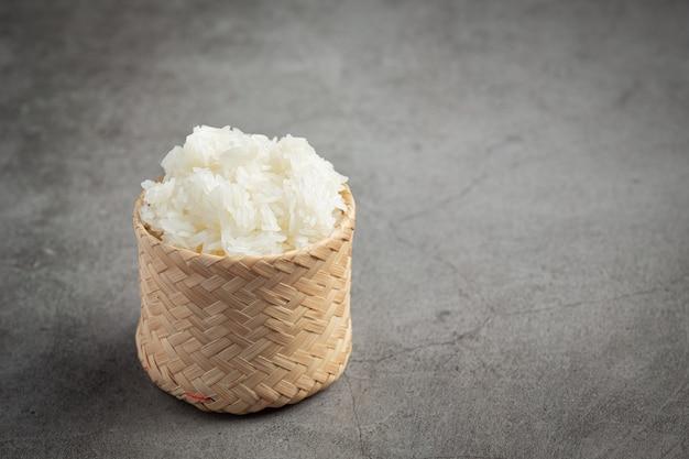 Riz gluant dans un panier en bambou mis sur un sol sombre