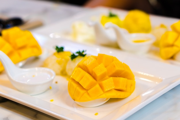 Riz gluant à la mangue dans un plat blanc avec mangue sélectionnée.