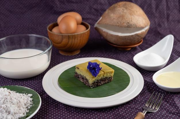 Riz gluant noir et crème anglaise sur une feuille de bananier dans une assiette blanche avec des fleurs de pois papillon.