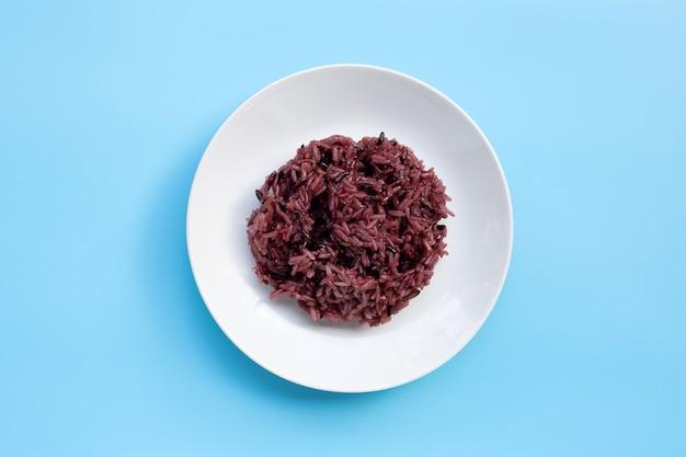 Riz gluant noir sur plat en céramique blanche sur fond bleu.