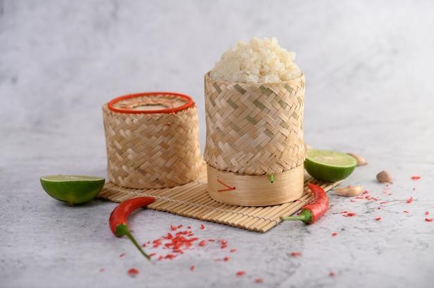 Riz gluant thaï dans un panier en bambou tressé sur un panneau en bois avec des piments, du citron vert et de l'ail