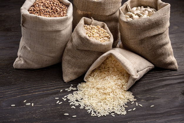 Riz, haricots et céréales dans des sacs sur une table en bois sombre.