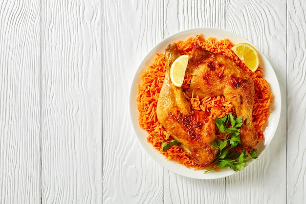 Riz indien à la tomate avec des quartiers de poulet rôtis cuits de riz basmati avec de la poudre de chili rouge, de la cannelle, de la cardamome, des clous de girofle, des quartiers de citron sur une assiette sur un fond en bois blanc, vue de dessus, espace pour copie