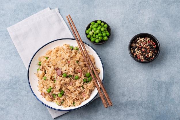 Riz japonais cuit avec des pois et des baguettes