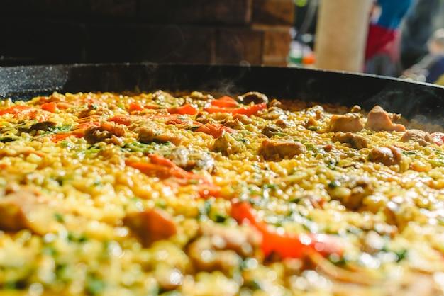 Riz et lapin, plat typique de la gastronomie de la région de murcie, en espagne, cuits dans une poêle à paella.