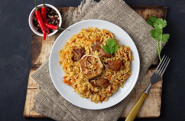 Riz, légumes et viande sur une assiette sur fond gris