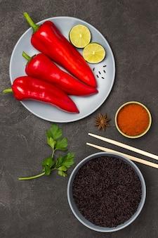 Riz noir dans un bol gris. poivron rouge et citron vert dans une assiette grise. bâtonnets de bambou et poivron rouge moulu dans un bol. mise à plat.