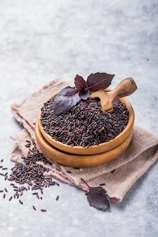 Riz noir non poli dans un bol en bois. fond de riz à grain long.