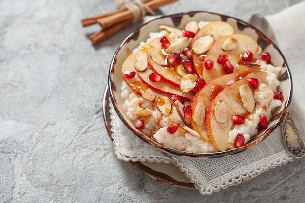 Riz à la noix de coco avec tranches de grenade, poire, cannelle et amande